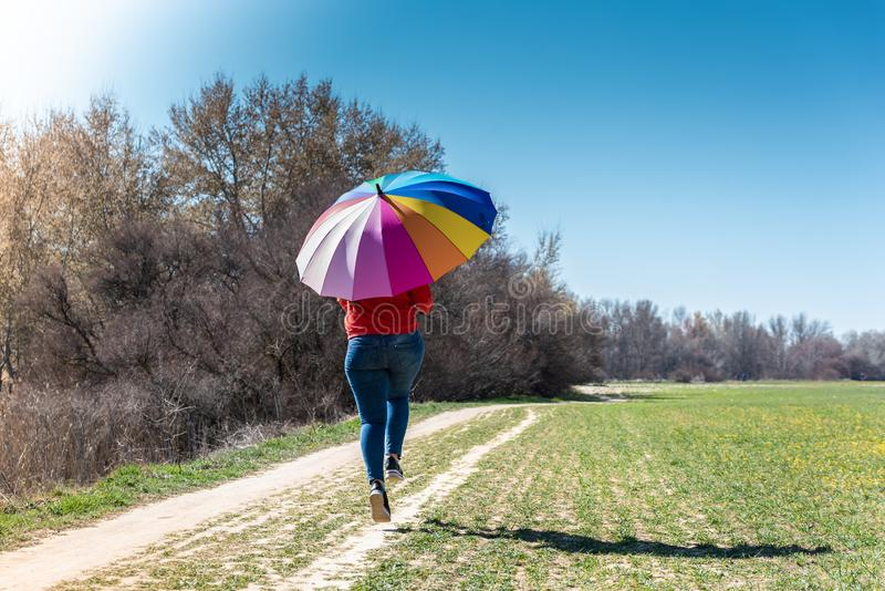 Young Woman Walking and Having Fun with an Umbrella stock photography