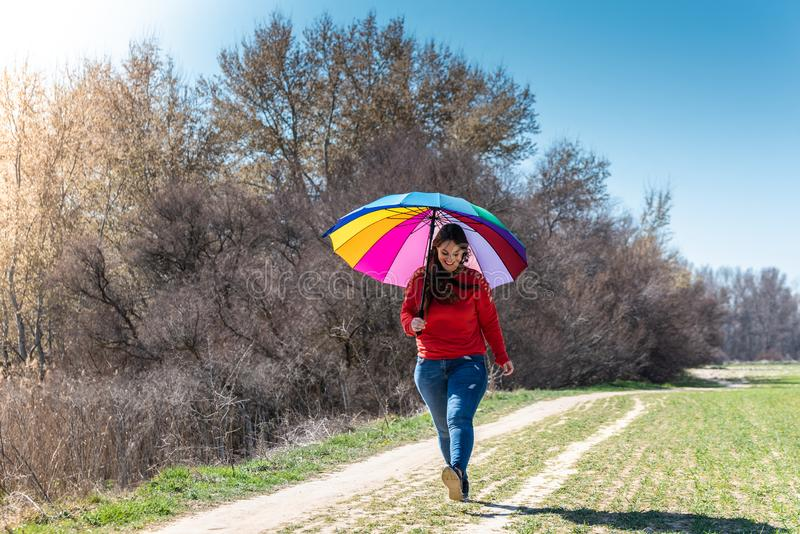 Young Woman Walking and Having Fun with an Umbrella royalty free stock images