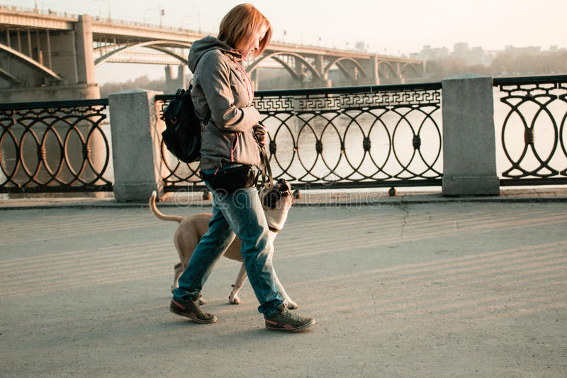 Young woman is walking with her dog in the evening park. royalty free stock photography
