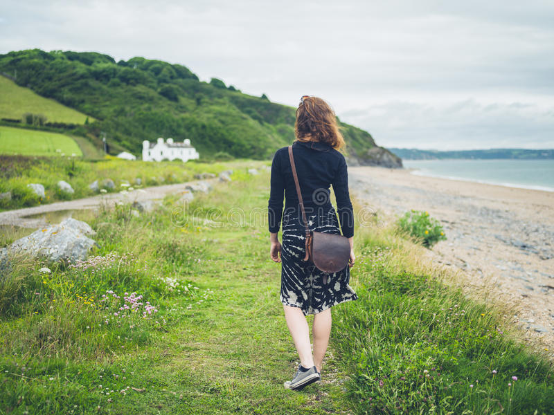 Young woman walking near the coast. A young woman is walking near the coast stock images