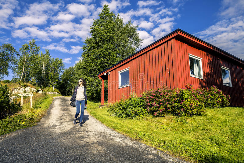 Young woman is walking near by red house, Norway. Young woman is walking on camping`s territory in Norway on sunny day stock photos