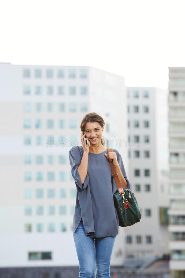 Young woman walking outdoors and talking on cell phone. Portrait of beautiful young woman walking outdoors and talking on cell phone royalty free stock photo