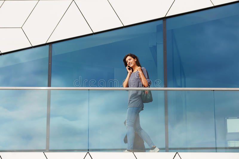 Young woman walking outdoors and talking on mobile phone. Portrait of young woman walking outdoors and talking on mobile phone stock photo