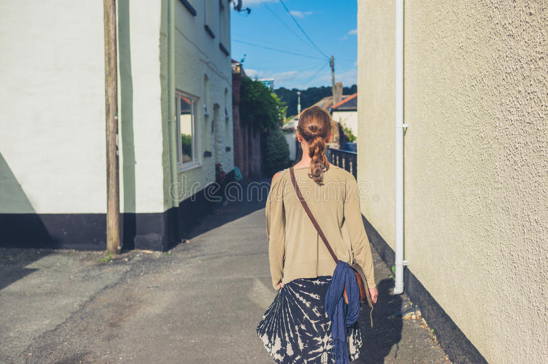 Young woman walking outside. A young woman is walking outside in a small town royalty free stock photography