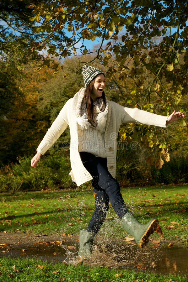 Young woman walking in the park and kicking a puddle of water stock photo