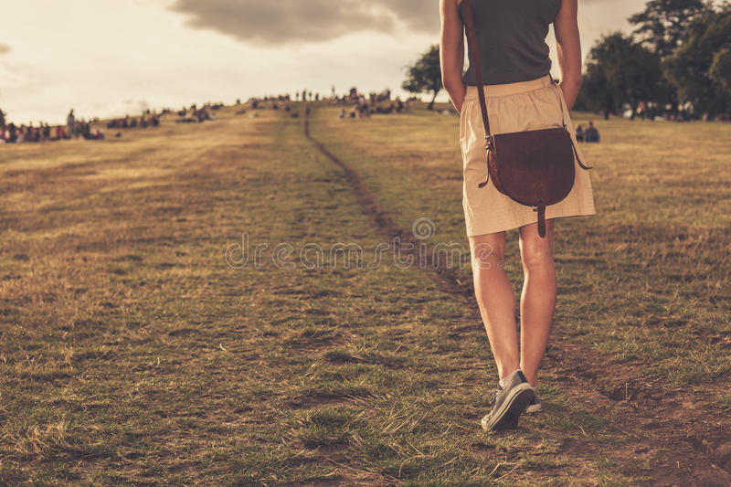 Young woman walking in the park at sunset stock photo