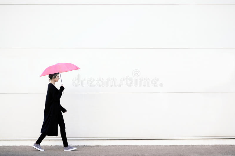 Young woman walking with pink umbrella. Young woman in black clothes walking with pink umbrella stock image