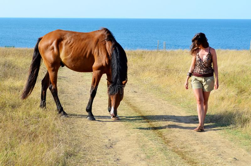 Woman and her Beautiful Red Wild Horse. Young woman walking with a red horse grazing in the meadow on the sea royalty free stock photos