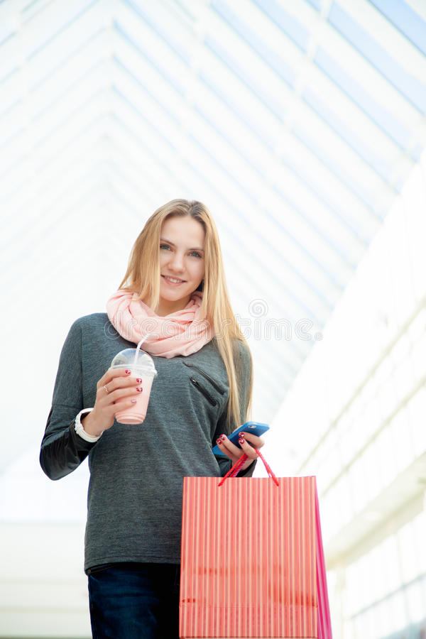 Young woman walking in shopping mall making a call with smartphone holding bags and a drink stock photography