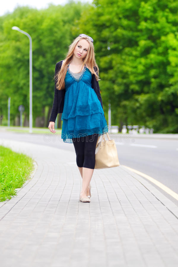 Young woman with walking on the sidewalk stock photos