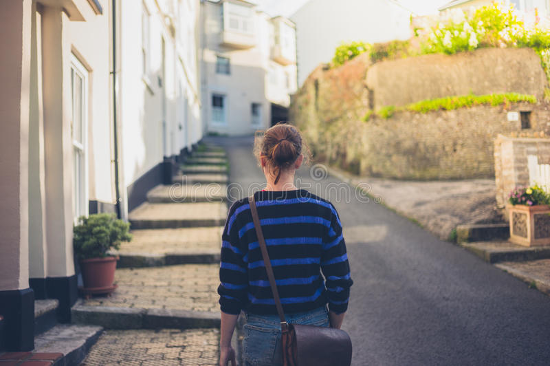 Young woman walking in small town. A young woman is walking in a small town stock photos
