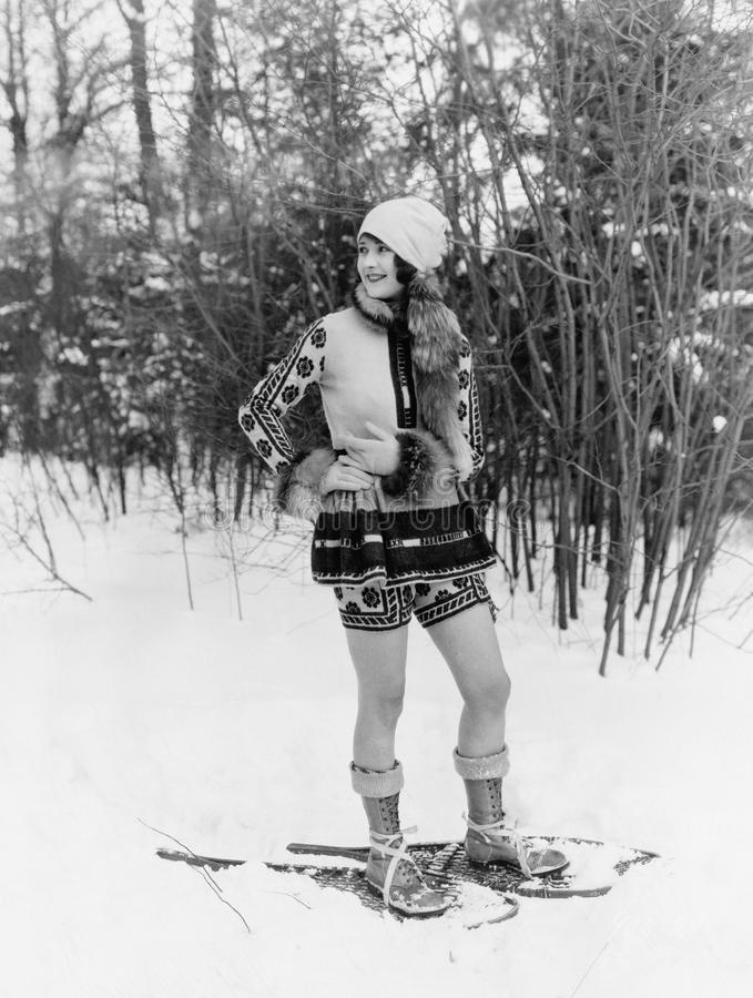 Young woman walking with snow shoes through the woods stock images