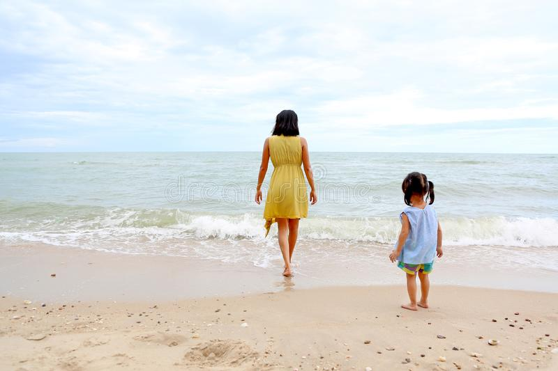 Young woman walking straight to the sea and her child girl standing on the beach royalty free stock photo