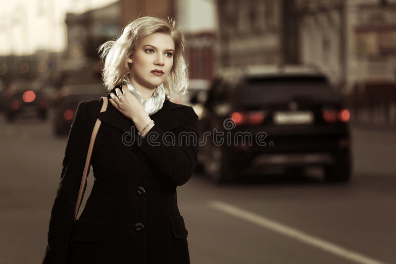 Fashion blond woman walking on the city street royalty free stock photos