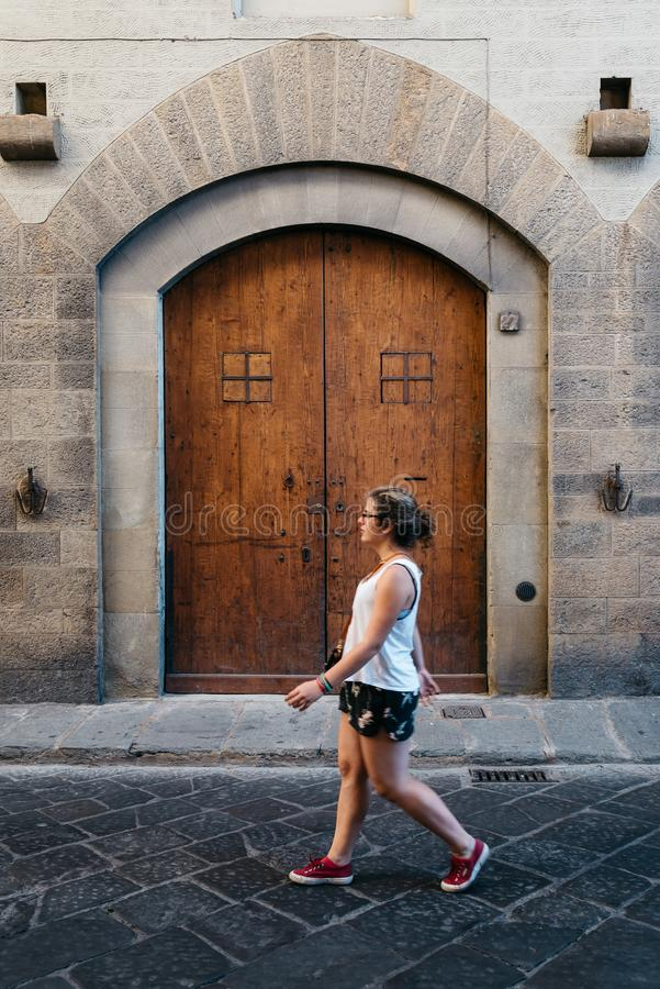 Young woman walking on the street against old arch door royalty free stock photo