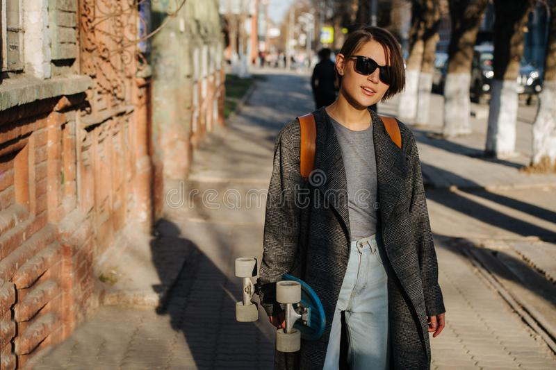 Young woman walking on the street holding skateboard. lifestyle photo. A young woman with short hair is walking on the street holding skateboard in one hand stock image