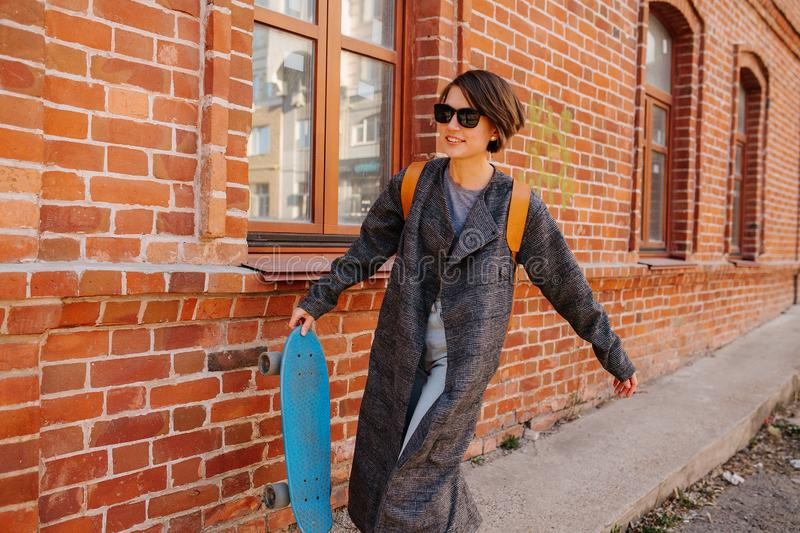 Young woman walking on the street holding skateboard. lifestyle photo. A young woman with short hair is walking on the street holding skateboard in one hand stock photography