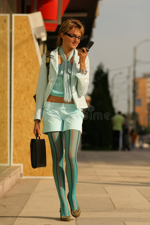 Young woman walking on the street and talking on the phone. Young woman walking on the street and reading a message SMS on the mobile phone royalty free stock photo