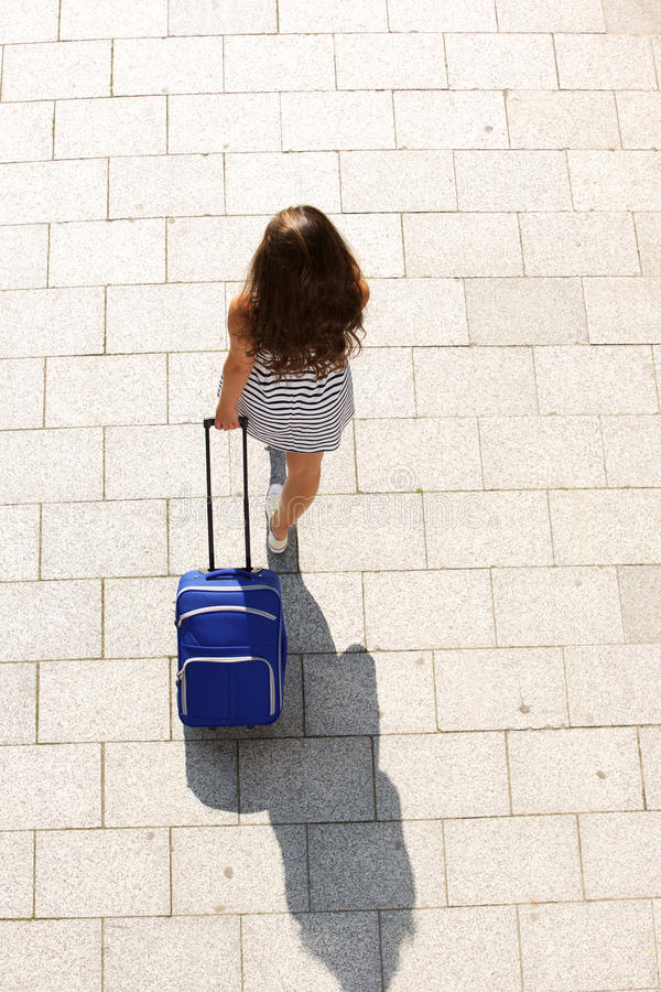 Young woman walking with suitcase royalty free stock photo