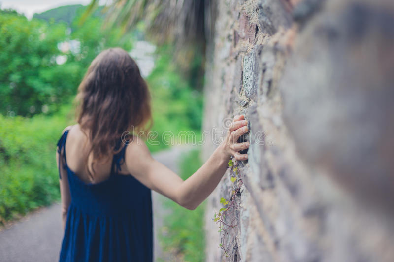Young woman walking by wall in countryside. A young woman is walking by a wall in the countryside royalty free stock images