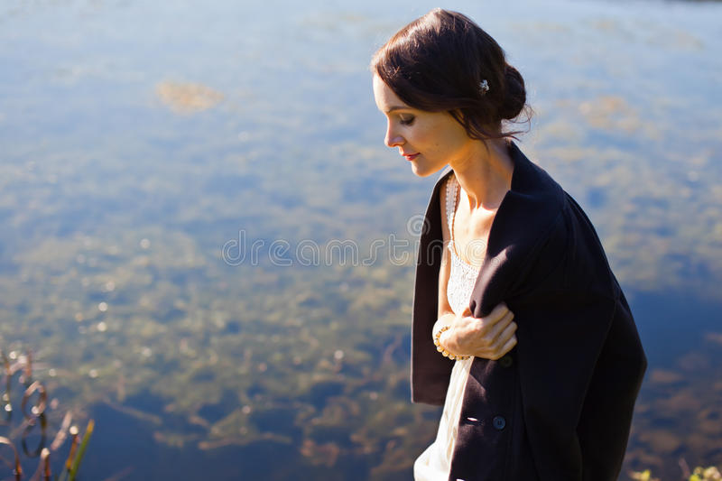 Young woman walking by water royalty free stock image