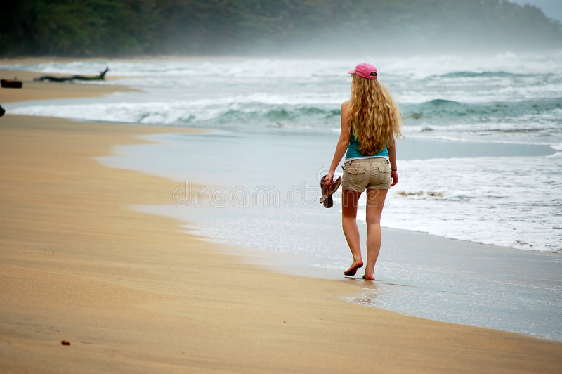 Download A Young Woman Walks Alone On The Beach Royalty Free Stock Image - Image: 4519576