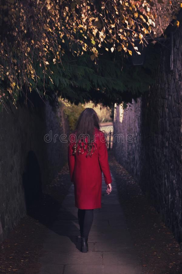 Woman in red coat walking through dark alley alone stock photography