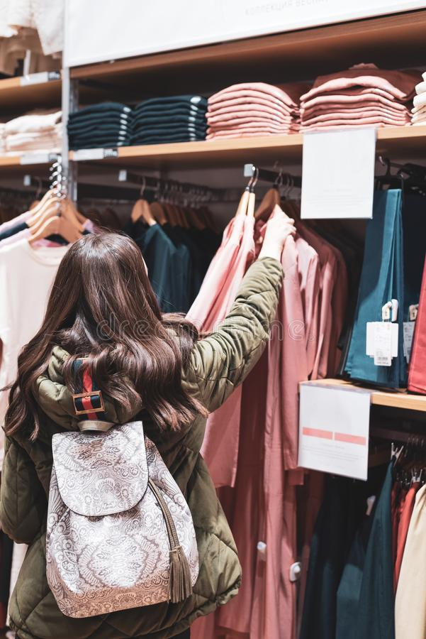 A young woman walks around the store and chooses a dress of pastel shades. Shopping concept royalty free stock image