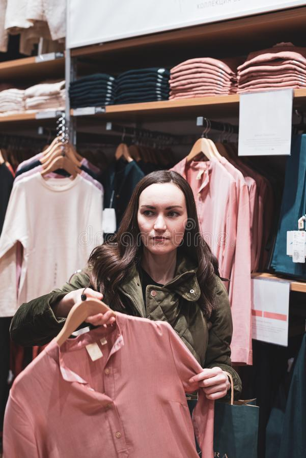 A young woman walks around the store and chooses a dress of pastel shades. Shopping concept stock photography