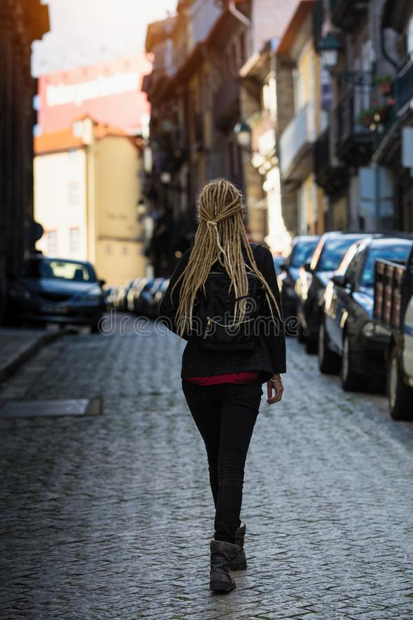 Young woman walks through the narrow pavement streets. stock images