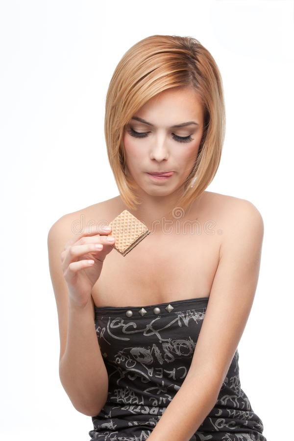 Young woman wanting to taste a wafer stock photos