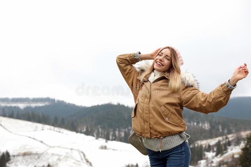 Young woman in warm clothes near snowy hill, space for text. Winter. Vacation royalty free stock images
