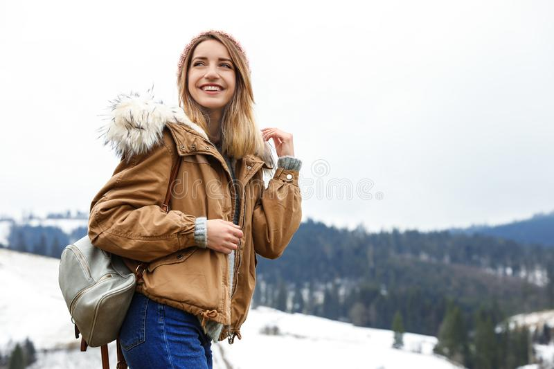 Young woman in warm clothes near snowy hill, space for text. Winter. Vacation stock photo