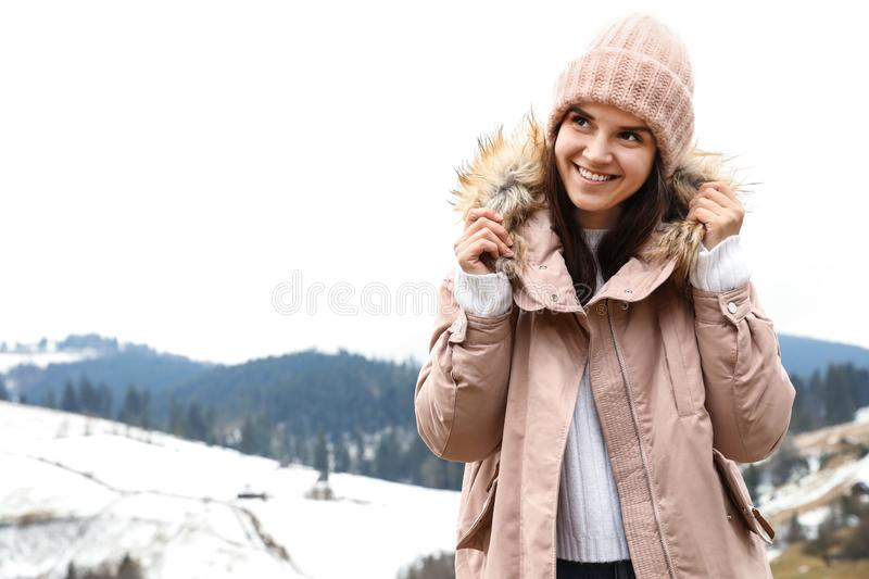 Young woman in warm clothes near snowy hill, space for text. Winter. Vacation royalty free stock photos