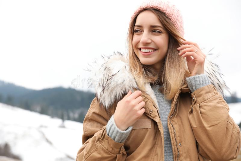 Young woman in warm clothes near snowy hill, space for text. Winter. Vacation royalty free stock image