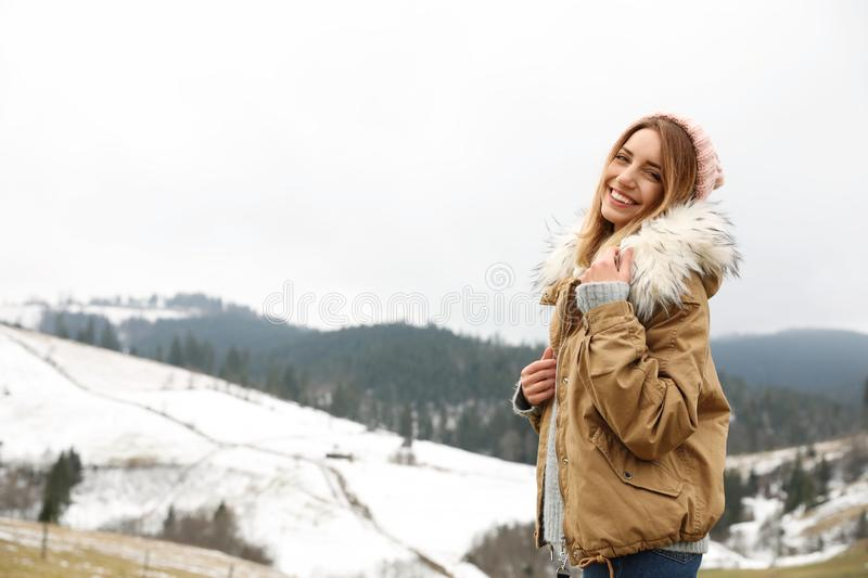 Young woman in warm clothes near snowy hill, space for text. Winter. Vacation stock photos