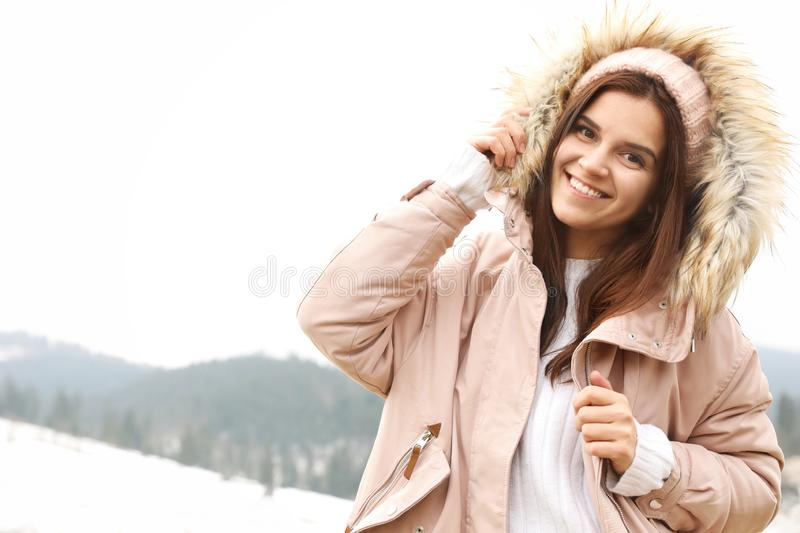 Young woman in warm clothes near snowy hill, space for text. Winter. Vacation royalty free stock photography