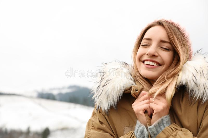 Young woman in warm clothes near snowy hill, space for text. Winter. Vacation royalty free stock photo