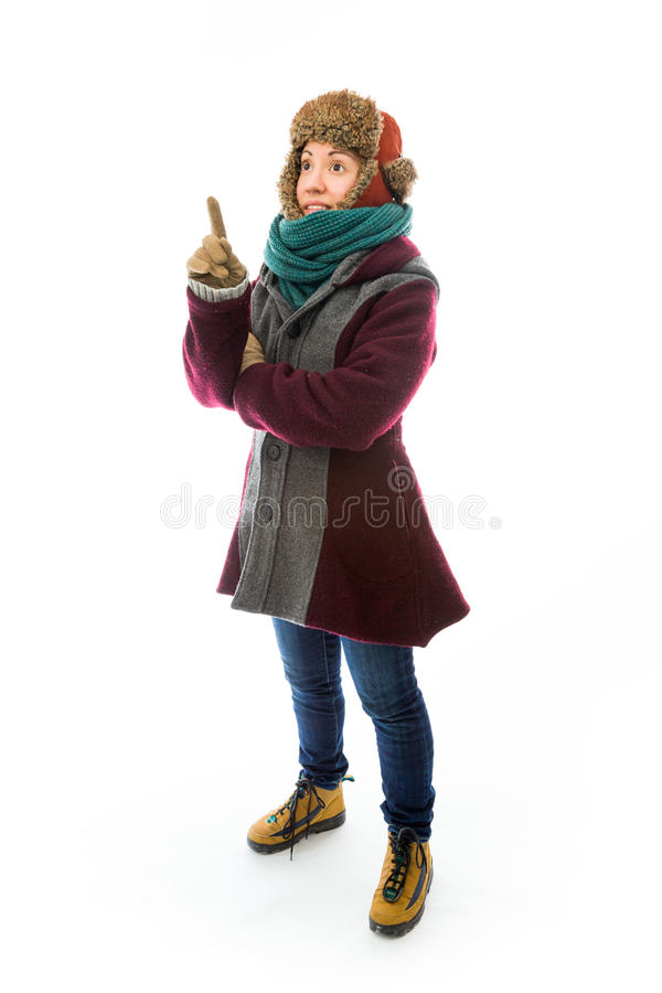 Young Woman In Warm Clothing And Pointing Upward Stock Photo