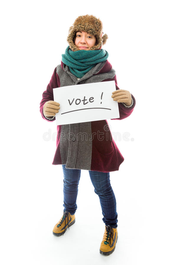 Young woman in warm clothing and showing vote sign on white back. Young adult caucasian woman isolated on a white background royalty free stock photo