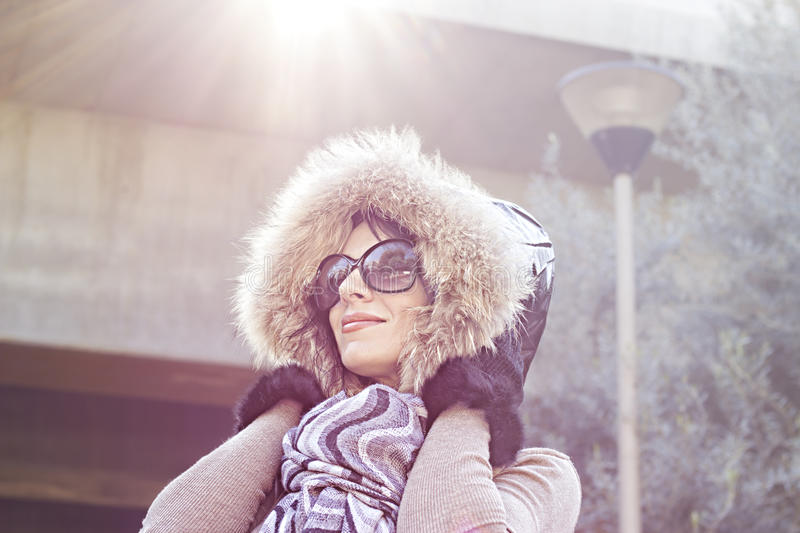 Young woman in warm hood on head outdoor enjoying sunlight on sunny day. royalty free stock images