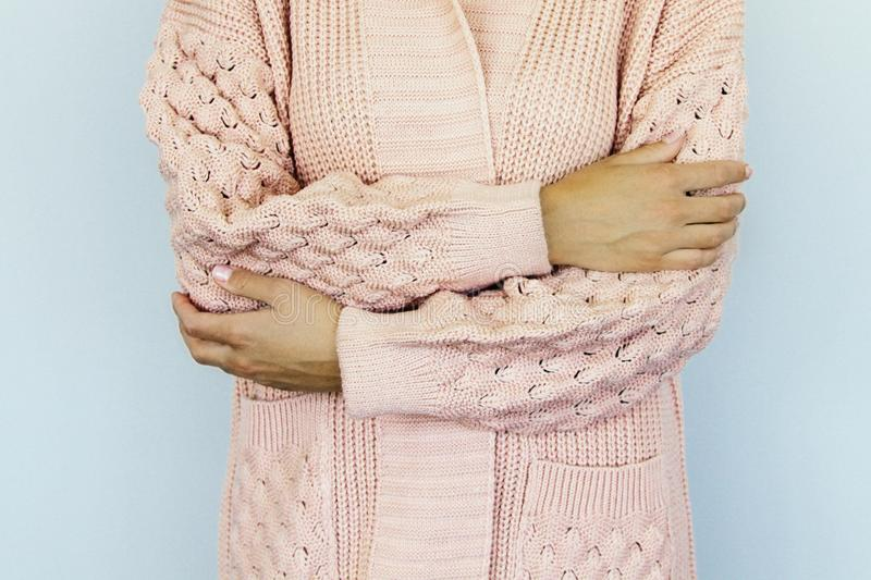 Young woman in a warm knitted sweater folded hands on the belt royalty free stock image