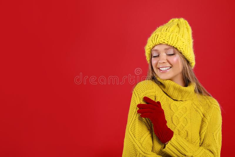 Young woman in warm sweater, gloves and hat on red, space for text. Winter season. Young woman in warm sweater, gloves and hat on red background, space for text stock photo