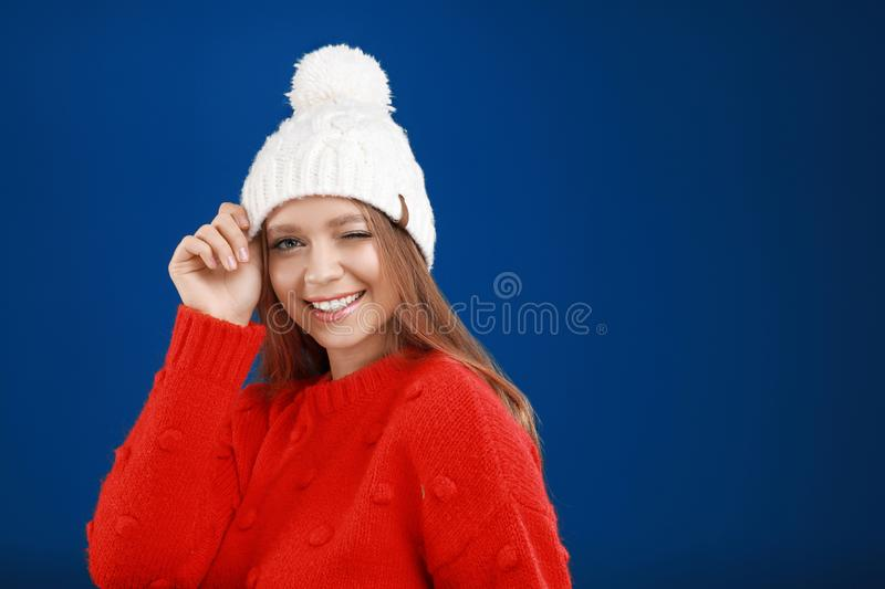 Young woman in warm sweater and hat on blue background, space for text. Winter season royalty free stock image
