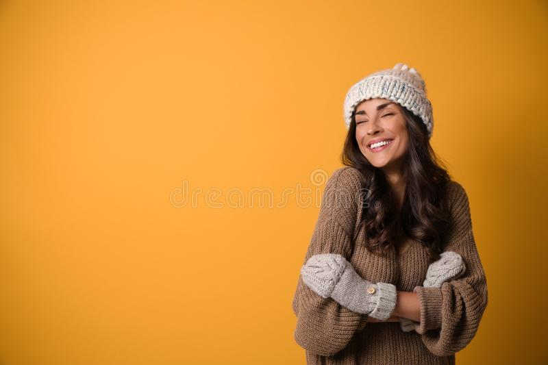 Young woman in warm sweater, hat and mittens on  background, space for text. Christmas season. Young woman in warm sweater, hat and mittens on yellow background royalty free stock photography