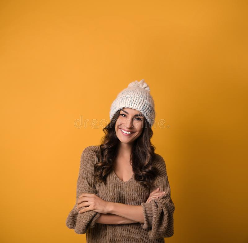 Young woman in warm sweater and hat on yellow , space for text. Christmas season. Young woman in warm sweater and hat on yellow background, space for text stock image