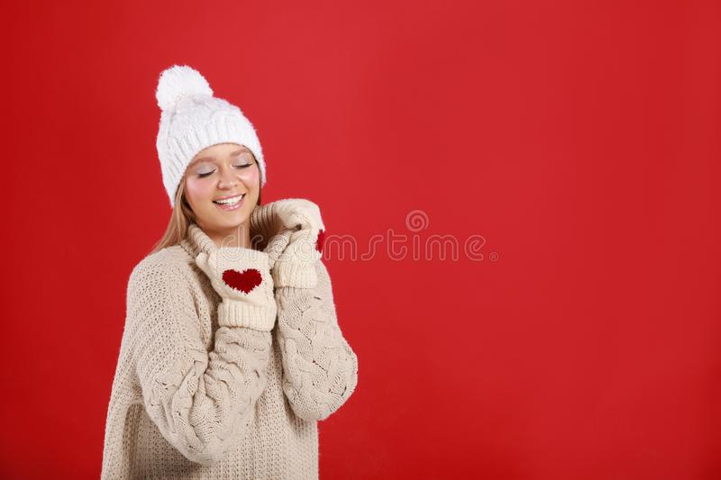 Young woman in warm , mittens and hat on red background, space for text. Winter season. Young woman in warm sweater, mittens and hat on red background, space for royalty free stock image