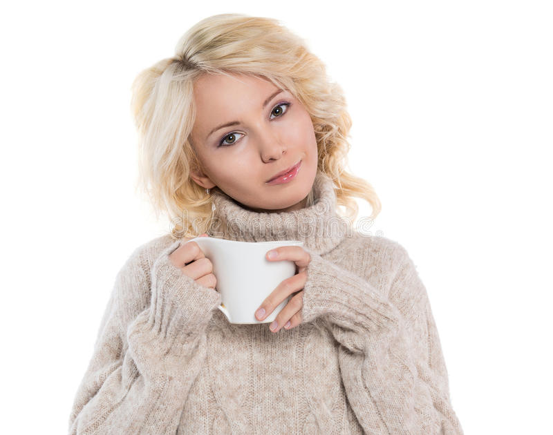 Young woman in a warm sweater and a mug in his hands. Beautiful, young woman in a warm sweater and a mug in his hands, isolated on white background royalty free stock photos