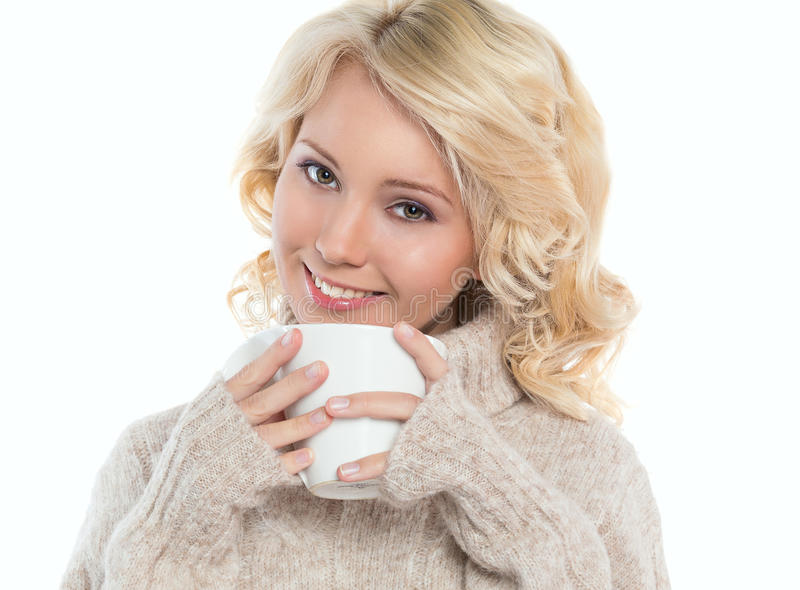 Young woman in a warm sweater and a mug in his hands. Beautiful, young woman in a warm sweater and a mug in his hands, isolated on white background stock photography
