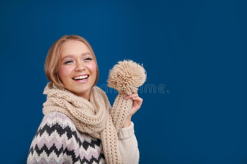 Young woman in warm sweater and scarf on background, space for text. Winter season. Young woman in warm sweater and scarf on blue background, space for text royalty free stock image